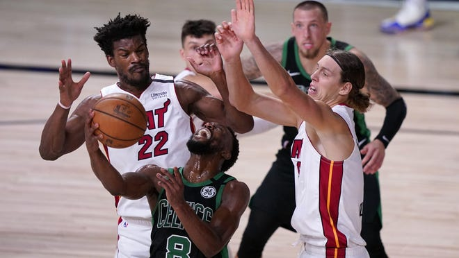 Boston Celtics guard Kemba Walker attempts to maintain control of the ball in front of Miami Heat forward Jimmy Butler (22) and Kelly Olynyk, right, during Thursday night's game in Lake Buena Vista, Fla.