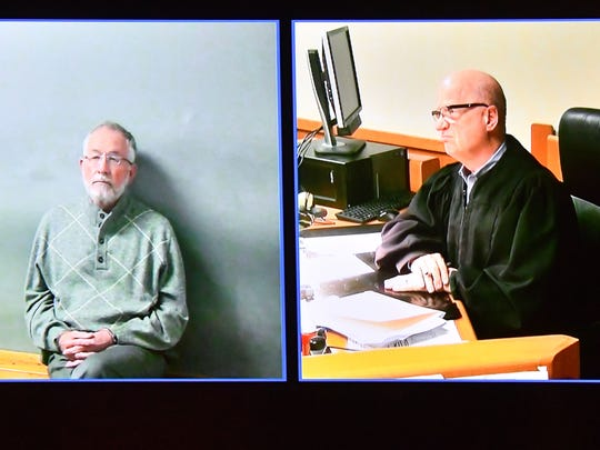 Judge Richard Ball (right) presides during video arraignment  of former MSU dean William Strampel (left) in 54-B court in East Lansing on Tuesday, March 27, 2018.