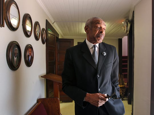 Rev. James Clinkscales, pastor of Royal Baptist Church in Anderson, looks at portraits of former pastors of the church on East Hampton Street near downtown Anderson.
