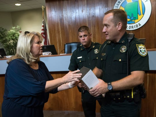 State Farm Agent Sale Leader, Cathy Robertson, left present Santa Rosa County Sheriff's Office Capt. Scott Haines, with a home security system at the Board of County Commissioner Board Room Wednesday, Aug. 23, 2017.