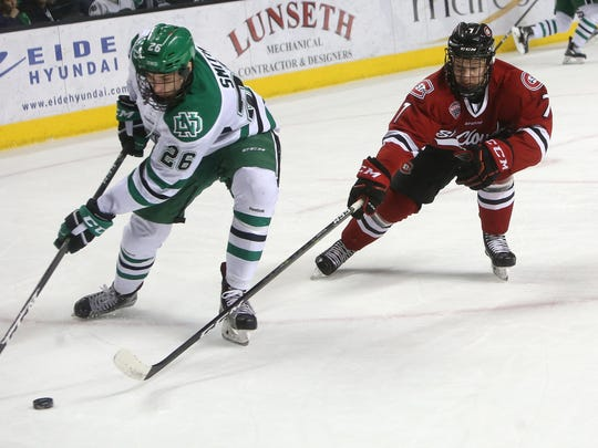 University of North Dakota forward Cole Smith (26) and St. Cloud State defensemen Niklas Nevalainen (7) chase the puck in the first period of Saturday's NCHC Quarterfinals game two between the Fighting Hawks and Huskies, March 11, 2017 at the Ralph Engelstad Arena in Grand Forks, N.D. (Jesse Trelstad/Grand Forks Herald)