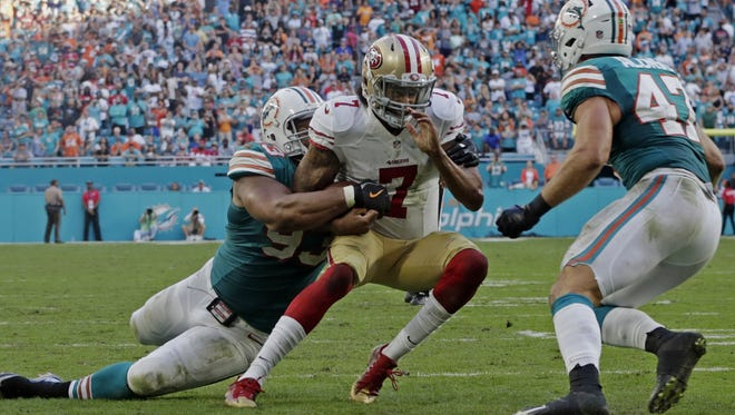 San Francisco quarterback Colin Kaepernick (7) is tackled by Miami's Ndamukong Suh (93) and linebacker Kiko Alonso (47) short of the end zone on the final play of Sunday's win by the Dolphins.