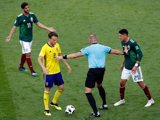 Referee Nestor Pitana from Argentina, second right, discusses with Mexico's Edson Alvarez, right, and Sweden's Albin Ekdal during the group F match between Mexico and Sweden, at the 2018 soccer World Cup in the Yekaterinburg Arena in Yekaterinburg , Russia, Wednesday, June 27, 2018. (AP Photo/Efrem Lukatsky)