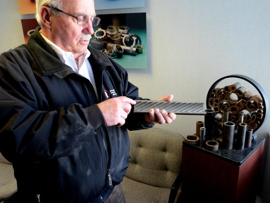 Les Whitver, vice president of South Lyon's Michigan Seamless Tube, looks at some of the McMunn Street business' products - a rifle tubing used in power plants - on Feb. 25. The company won an award from the South Lyon Chamber of Commerce for its come-back success story.