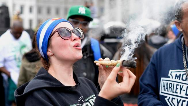 """DENVER, CO - April 18: Abby Lindsay blows out smoke after smoking on a large joint on Saturday, April 18, 2015 at Civic Center Park in Denver, Colorado. The annual 420 Rally once again brought over a thousand smokers and music lovers to the park to celebrate the """"holiday"""" which this year spans over the weekend. Musical acts this year included Too Short and Devin The Dude."""