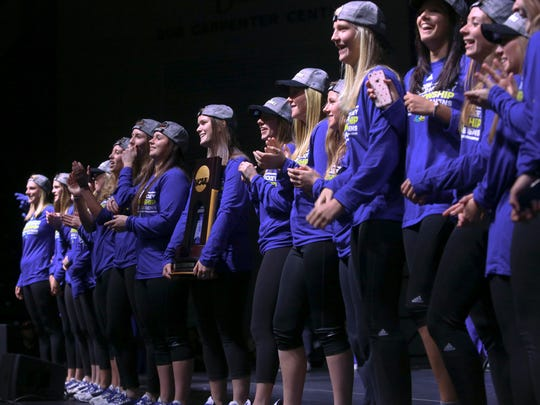 University of Delaware field hockey team members, including Kayla Devlin, holding the NCAA championship trophy, take in applause from the crowd during an event celebrating the team's first NCAA title at the Bob Carpenter Center Friday.