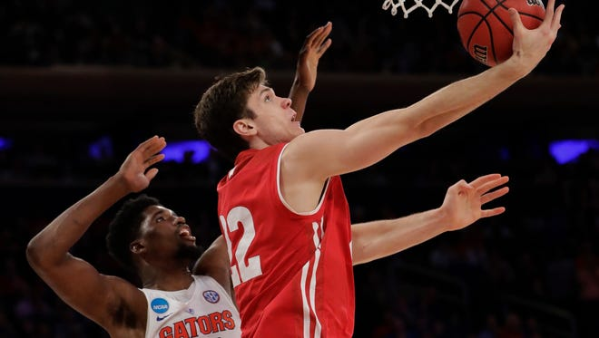 Wisconsin forward Ethan Happ (22) puts up a shot against Florida forward Kevarrius Hayes (13) in the second half of an East Regional semifinal game of the NCAA men's college basketball tournament, Friday, March 24, 2017, in New York. (AP Photo/Julio Cortez) ORG XMIT: MSG200