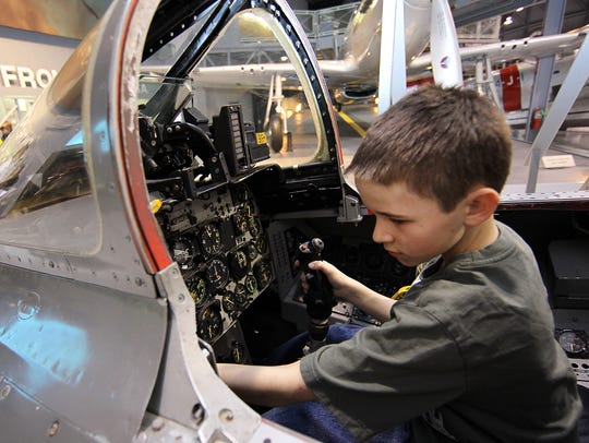 Bryce Barnes sits inside a F-100 cockpit trainer while