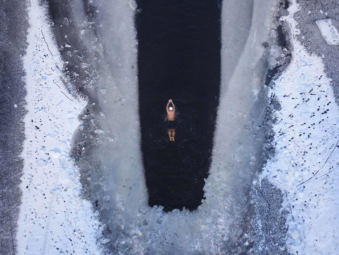 A man swims in a partly frozen lake, Dec. 10, 2018,