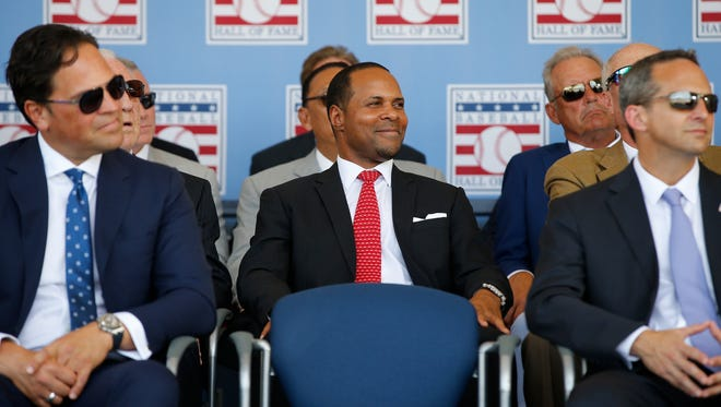 Reds great and Hall of Famer Barry Larkin, center, smiles as he listens to former Seattle Mariners and Cincinnati Reds player, Ken Griffey Jr.'s, speech during the induction ceremony into the National Baseball Hall of Fame, Sunday, July 24, 2016, at the Clarks Sports Center in Cooperstown, N.Y.