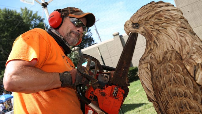 Kieth Gregory of Grizzly Mountain Saw Works carves an eagle during Cider Days on Walnut Street.