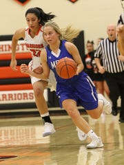 Kayla Jacobson of St Thomas More drives past the defense
