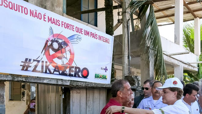 A hand out picture released by Brazilian Presidency shows Brazilian President Dilma Rousseff (R) taking part in an awareness campaign during the day of national mobilization against the Aedes aegypti mosquito --that transmits dengue, chikungunya fever and zika virus-- in the neighborhood of Santa Cruz in Rio de Janeiro, Brazil, on February 13, 2016.