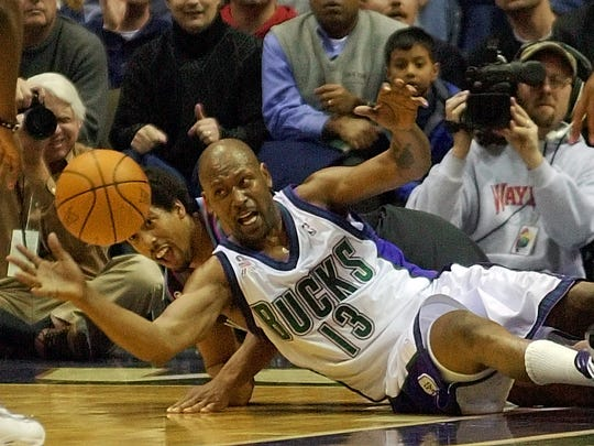 Milwaukee Bucks' Glenn Robinson (13) and Cleveland Cavaliers' Andre Miller go to the floor after a loose ball in the third quarter Wednesday, Feb. 13, 2002, in Milwaukee.