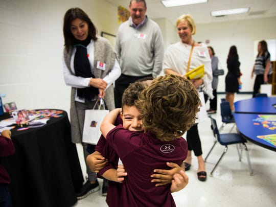 Sebastian Valderrama, center, spins around in a hug with his friends at the YMCA booth during the Naples Winter Wine Festival's Meet the Kids Day at the Boys & Girls Club of Collier County in Naples on Friday, Jan. 26, 2018.