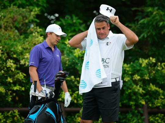 Vestal graduate Jay Danzi, right, carried the clubs on a hot and humid day for Jordan Spieth at the SMBC Singapore Open. Danzi is Spieth's agent and was filling in for caddie Michael Greller, who is injured.