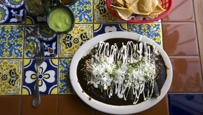 Enmoladas at La 15 y Salsas Mexican Grill in Phoenix are similar to enchiladas, except they use a mole sauce instead of a chile sauce.
