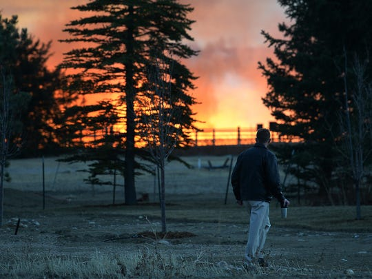 A man watches a grass fire at Castle Rock Lane and South Timberline Road southeast of Fort Collins on Feb.10.