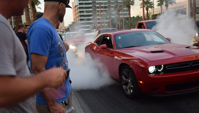 A Dodge Challenger lights 'em up for the crowd lining several miles of Central Avenue.