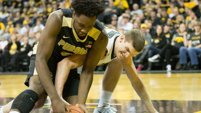 Iowa's Adam Woodbury and Purdue's Caleb Swanigan scramble for a loose ball during the first half at Carver-Hawkeye Arena.