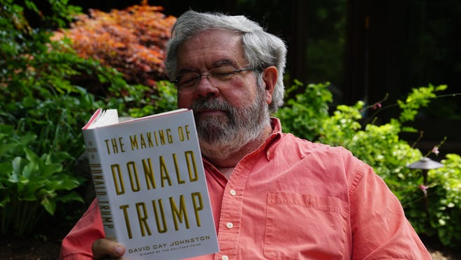 """David Cay Johnston looks over a copy of his new book, """"The Making of Donald Trump."""""""
