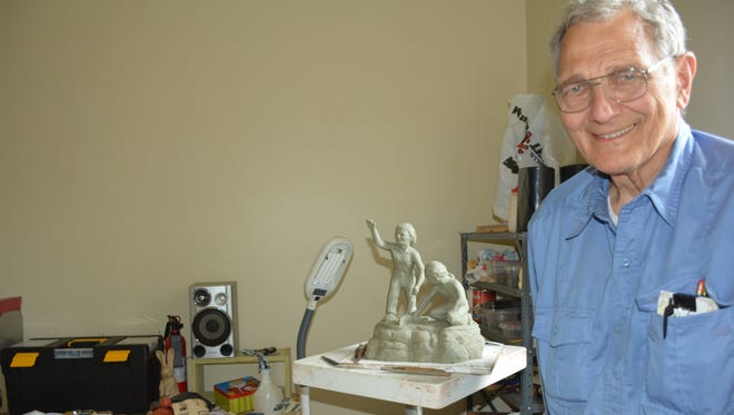 Dr. William Faller in his studio with a model of his proposed sculpture of two Native Americans boys.