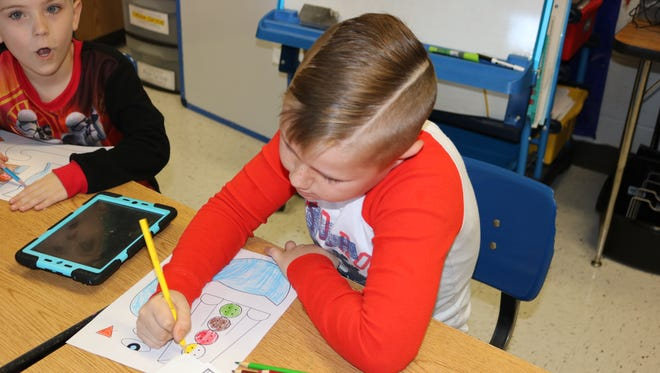 MES student Garrison Thomas focuses in on his reading activity last year.
