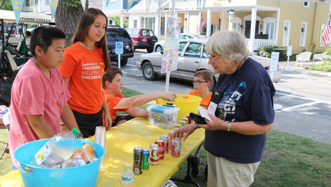 Martha Wason, right, buys a refreshment from the charity lemonade stand started by local teens Molly McNamara and Logan Martens, which has raised more than $80,000 to prevent malaria in Africa.