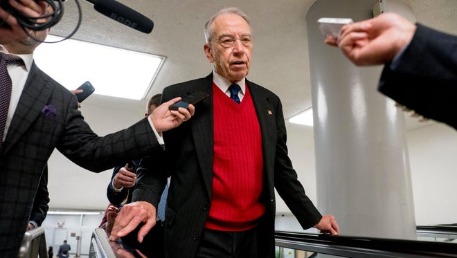 Sen. Chuck Grassley, R-Ia., speaks to reporters as he walks through the Senate subway on Capitol Hill on Dec. 6.