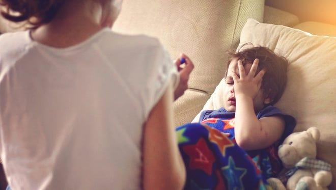 A mother checks her son's temperature.