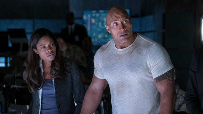 """This image released by Warner Bros. shows Naomi Harris, left, and Dwayne Johnson in a scene from """"Rampage."""" (Frank Masi/Warner Bros. via AP)"""