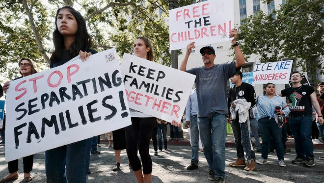 Protesters carry signs and chant slogans Tuesday in Los Angeles during an immigrant-rights protest.