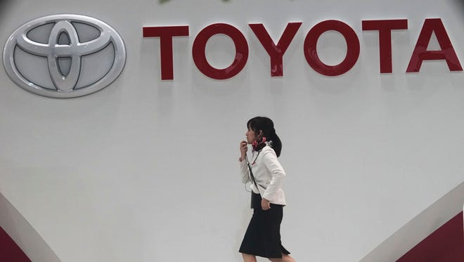 A worker walks past the Toyota logo at a gallery in Tokyo, on Nov. 5, 2014.