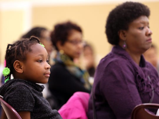 Loreal Bond, 6, and Annette Dancer, right, listen to