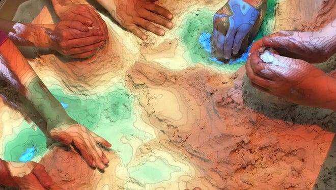 As children sculpt mountains and valleys out of sand, a computer and 3D scanner animates rain and flowing rivers onto the sand in real time.