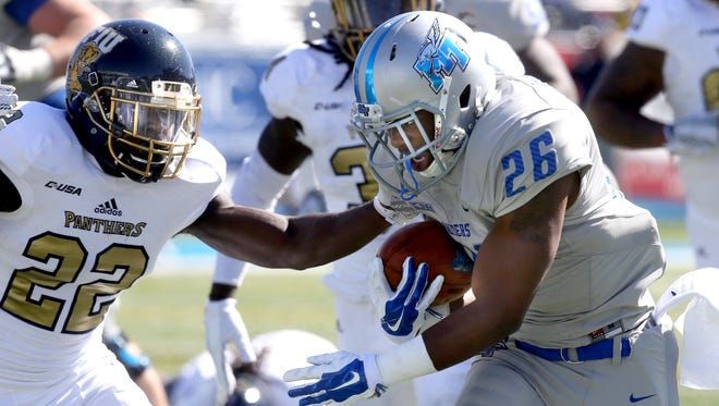 MTSU's Kamani Thomas (26) runs the ball as FIU's Mark Bruno  (22) tries to stop Thomas during the NCAA college football game on Saturday, Oct. 17, 2015, in Murfreesboro, Tenn.