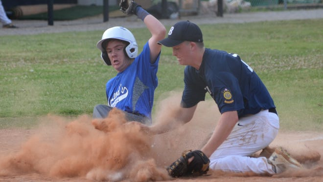 Mountain Home MacLeod's Kollin Kendrick slides safely into home plate as Batesville pitcher Kyle Long loses the ball in the dirt Tuesday at Batesville.