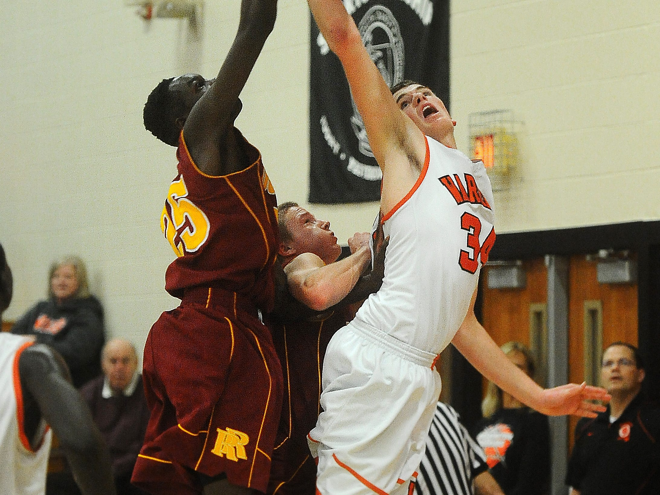 Washington's Cole Benson goes up for a shot while Roosevelt's Mayuen Akok (left) and Jett Thune defend during their game at Washington High School on Tuesday, Dec. 16, 2014.