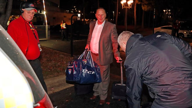 Gerard Gallant, center, former Florida Panthers head coach, approaches a cab after being relieved of his duties following an NHL hockey game against the Carolina Hurricanes, Sunday, Nov. 27, 2016, in Raleigh, N.C.