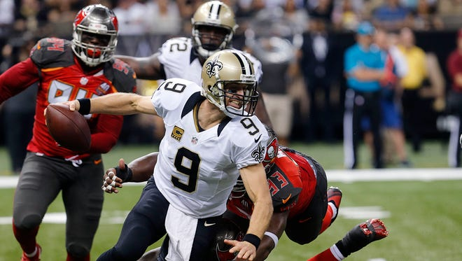 New Orleans Saints quarterback Drew Brees (9) is dragged down as he scrambles in the first half of an NFL football game against the Tampa Bay Buccaneers in New Orleans, Sunday, Sept. 20, 2015. (AP Photo/Bill Haber)