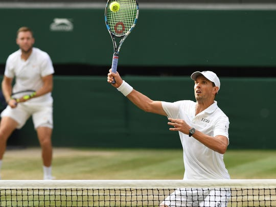 Camarillo's Mike Bryan hits a volley while partner