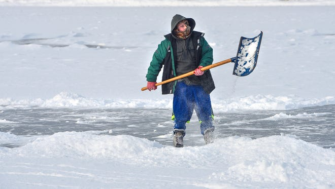 Hunter Tong shovels newly-fallen snow Monday, Jan. 15, 2018, from the ice on Lake George so that he can have a place to skate.