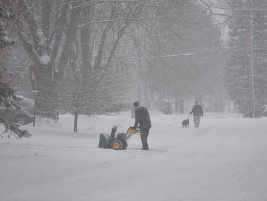 A man gets a jump on clearing his driveway with a snowblower