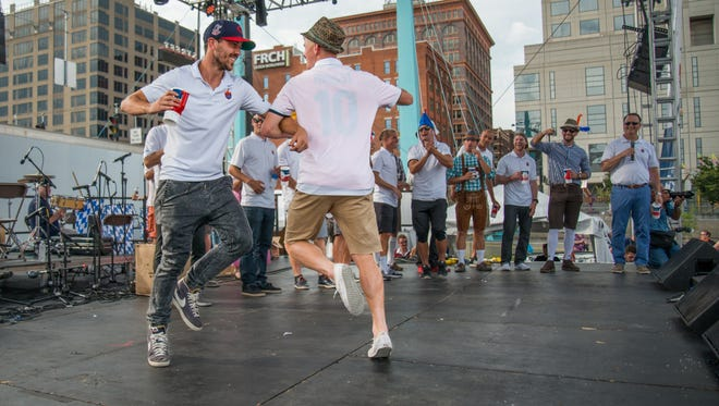 FC Cincinnati players Jimmy McLaughlin, right, and Andrew Wiedeman dance on stage as they are called up with other FC players before the world's largest chicken dance during Oktoberfest Sunday September 18, 2016.