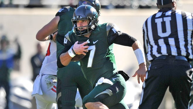 Michigan Statequarterback Tyler O'Connor, who got the start again, fakes a handoff and runs for a first down in the victory Saturday.