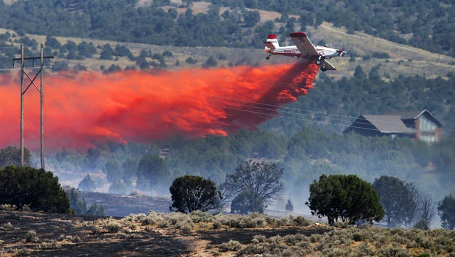 A small air tanker drops retardant on a fire burning in Stockton, Utah, on Wednesday. Officials say a wildfire encroaching on homes in the Tooele County town of Stockton has overtaken 400-500 acres. Utah Division of Forestry, Fire and State Lands spokesman Jason Curry says he believes no homes have been destroyed.