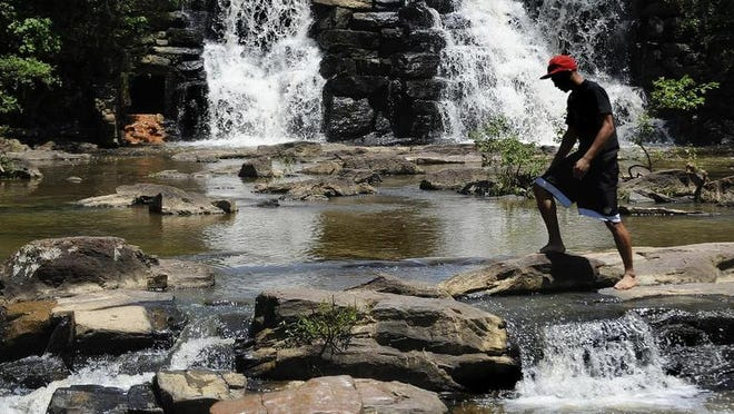 A visitor walks across the rocks at Chewacla State Park in Auburn. There are 22 state parks sprinkled across Alabama.