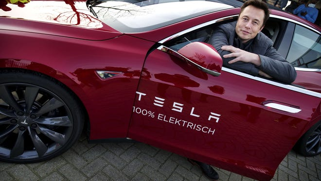 Elon Musk, CEO of American electric vehicle manufacturer Tesla Motors, poses with a Tesla during a visit to Amsterdam
