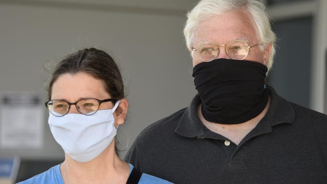 Susan and Vincent Ferrara wear their masks as they exit the Municipal Building in Augusta Tuesday.