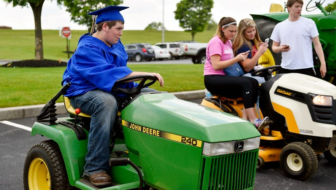 Kennard-Dale senior Travis McFatridge parks his tractor before leaving with other classmates on tractors Thursday, May 19, 2016, outside the school in Fawn Grove. Seniors got to drive farm tractors to and from school.